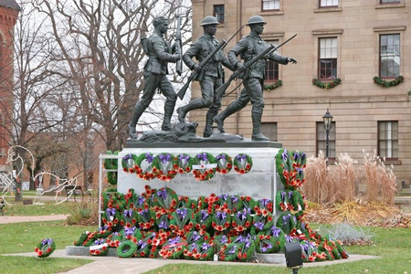 l first: Remembrance Day wreaths placed at the base of a war memorial to the veterans of the first and second world war.  Monument is located in Charlottetown, Prince Edward Island, Canada. Editorial
