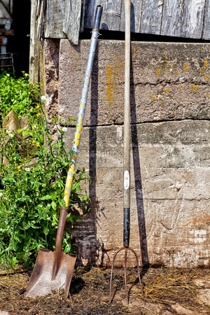 Tools used to clean up barn manure (the manual way) leaning up against an old barn.