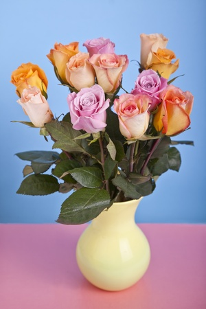 A ceramic vase filled with a valentine assortment of pastel pinks and orange roses. photo