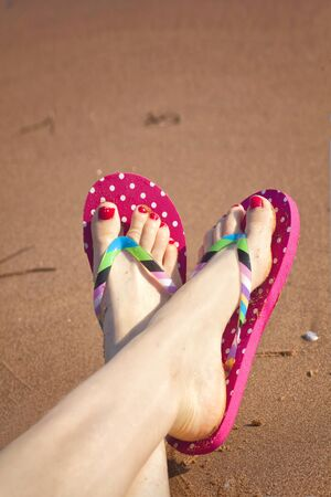 Painted toes and flip flops on a sandy beach