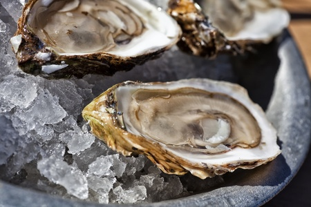 A platter of fresh raw oysters on ice at an outdoor cafe.