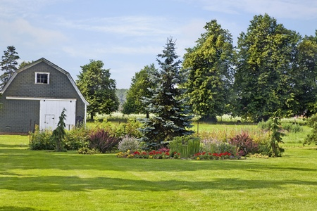 An ornamental garden with conifers and flowers in a rural farm setting.
