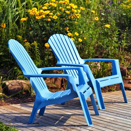 adirondack chair: Brilliant blue plastic outdoor Adirondack chairs on the deck in a summer garden.