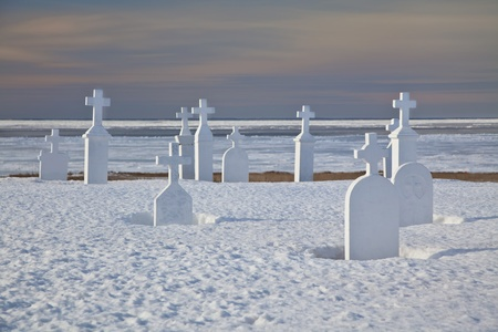 Cemetery along the shore with the ocean and ice in the background.