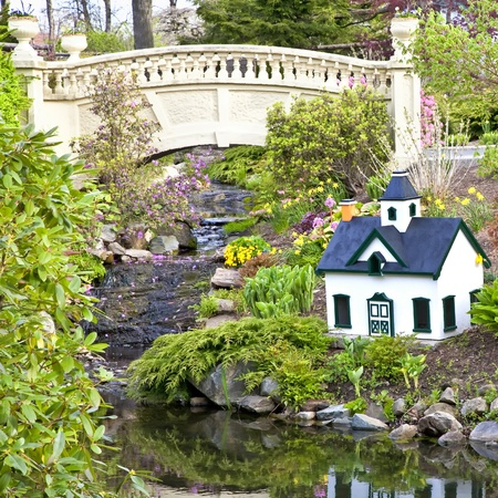 A public garden in Halifax, Nova Scotia featuring a small stream, garden bridge and a minature model house. photo