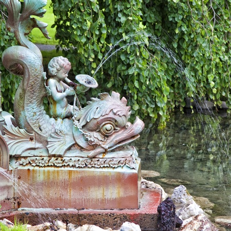 Fountain detail with a cherub and a stylized fish.