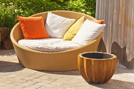 furniture: A modern wicker garden sofa or love seat in the home garden.  Stock Photo