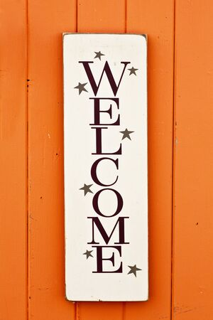 A folksy styled wooden Welcome sign on the side of a brightly colored wooden building. photo