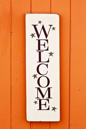 welcome door: Un cartello in legno in stile rustico 'Welcome' sul lato di un luminoso edificio in legno colorato.