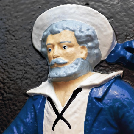 A painted figure of a sailor on a cast iron plaque.  Plaque is found in the Halifax Public Gardens in Halifax, Nova Scotia, Canada. photo
