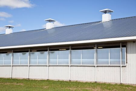 vents: North American modern commercial dairy barn with a galvanized steel roof. Stock Photo