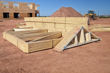 Roof rafters stacked up on a construction site for a large building and waiting for installation. Stock Photo - 13446048