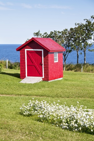 Red garden shed overlooking the ocean.