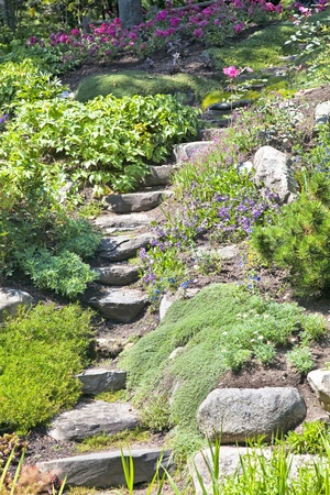 Stone stairs going up a small hill in a perennial rock garden. photo