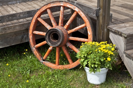 An old wagon wheel used as an outside decoration for a home deck. photo