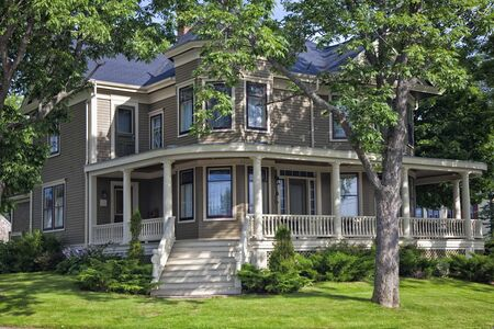 Classic older north American home surrounded by shady trees