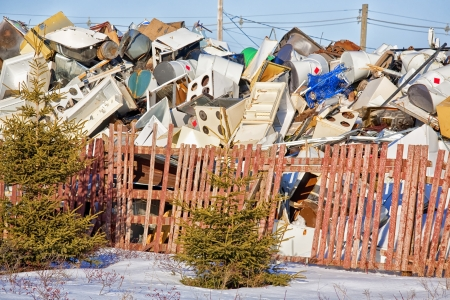 An accumulation of appliances and other large pieces of refuge in a garbage dump. photo