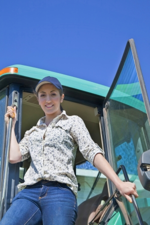agrarian: A young woman farmer stepping out of the cab of her tractor  Stock Photo