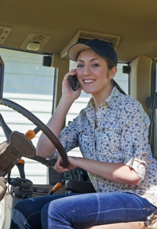 Young woman farmer speaking on her phone in the cab of her tractor
