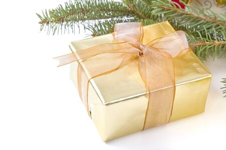 A Christmas gift decorated in gold wrapping paper and a gold fabric bow.