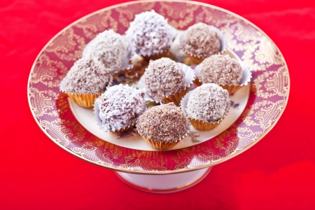 coconut sugar: An assortment of homemade Christmas truffles each coated in special toppings. Each in its own foil cup on a special Christmas serving platter. Stock Photo