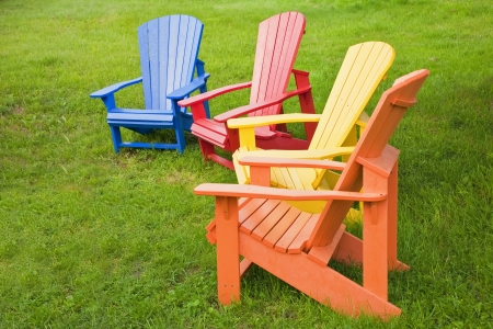 A group of Adirondack chairs painted in brilliant colors. photo