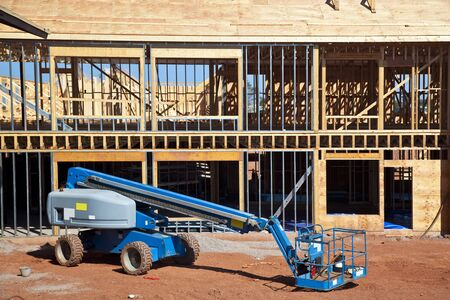 telescopic: A boom lift with a telescopic arm on a construction site.