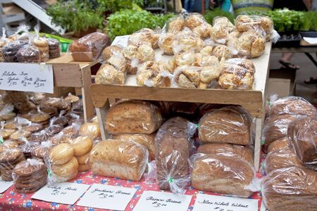 Various types of bread and other baked goods at a farmers market bake sale.