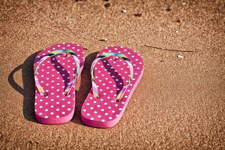 Pink polka dotted flip flops on the beach. photo