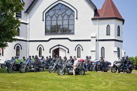 Indian River, Prince Edward Island, Canada - June 29, 2012: Members of a motorcycle tour drive through the island during the Atlanticade Motorcycle Rally 2012 in Prince Edward Island, Canada, stopping at Indian River Church.  Approximately 12,000 people a
