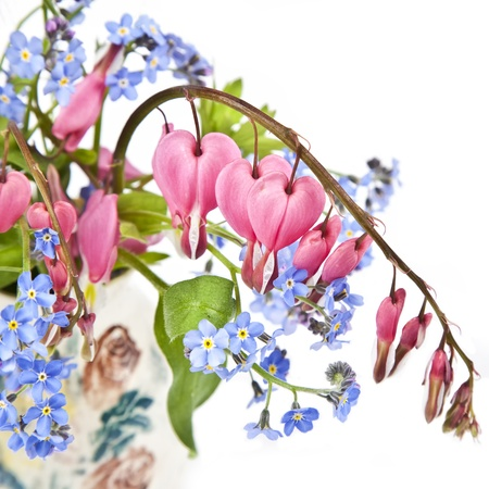 A bouquet of bleeding hearts and forget me nots in a small pottery vase  photo