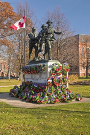 remembrance day poppy: War memorial erected in Charlottetown, Prince Edward Island, Canada pictured after a Remebrance Day service   This   public monument erected shortly after the First World War  to commemorate fallen soldiers from PEI   It was the work of the Canadian sculp