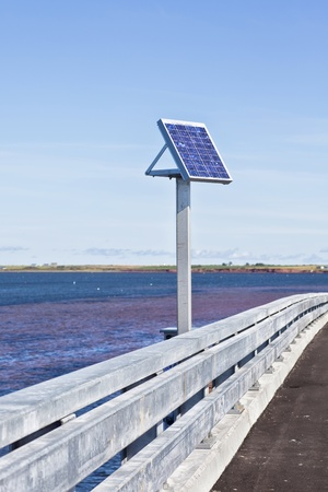 eco building: Small solar panel on the side of a bridge.