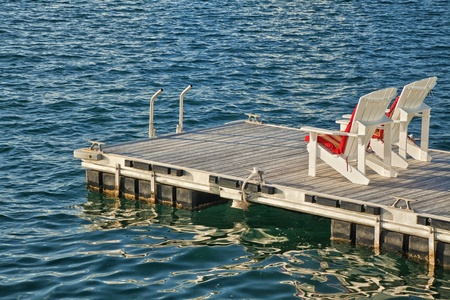 Two adirondack chairs on a floating dock. photo