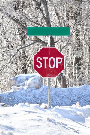 snowbank: Stop sign in the middle of a snowbank and covered in ice and icicles.