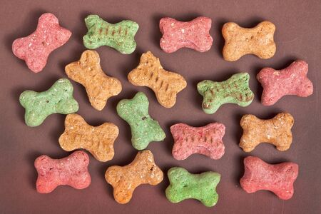 Small multi colored dog biscuits scattered at random on a brown background. photo