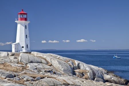 lobster: Peggys Cove lighthouse, Nova Scotia, Canada.  Lobster boat gathering traps in the background. Stock Photo