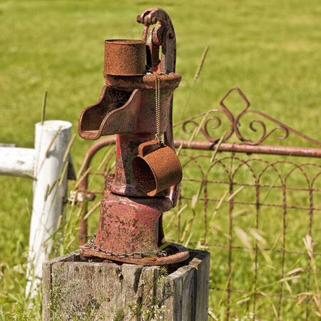 garden fountain: An old rusty water pump with its own rusty tin mug. Stock Photo