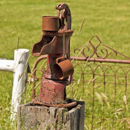 bomba de agua: Una vieja bomba de agua oxidada con su propia taza de hojalata oxidada. Foto de archivo