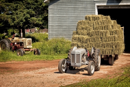 Vintage tractor hauling a wagon load of hay bales. photo