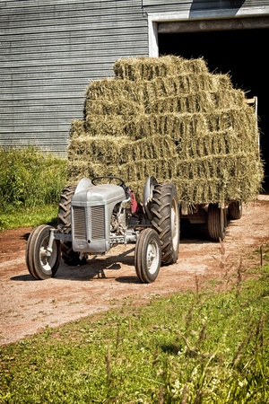 old tractors: Vintage tractor hauling a wagon load of hay bales.