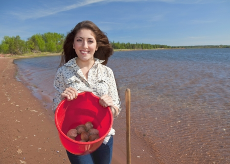 Young woman with her shovel digging clams. photo