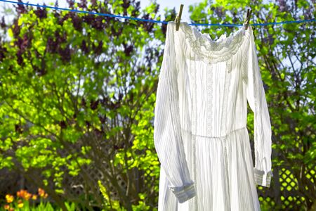 A white lacey vintage dress hanging on a cloths line with strong backlighting. photo