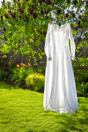 lacey: A white lacey vintage dress hanging on a cloths line with strong backlighting.
