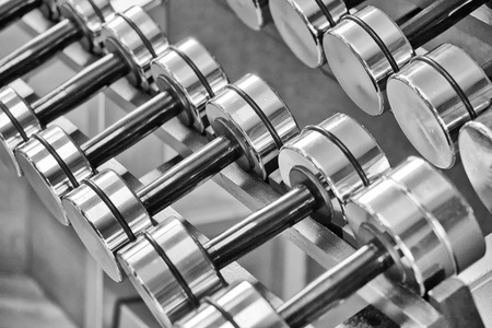 free weight: A rack of silver colored dumbells.