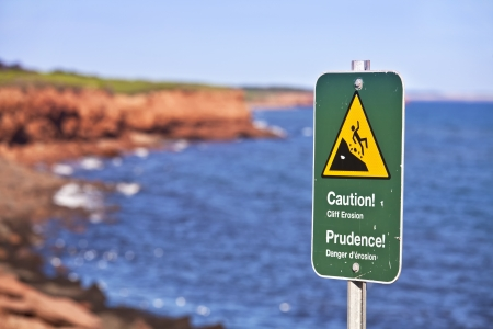 steep cliffs sign: Danger sign on eroding cliffs of the National Park on the north shores of Prince Edward Island, Canada.