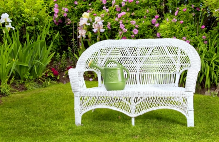 rattan: White wicker love seat with watering can in the summer garden.