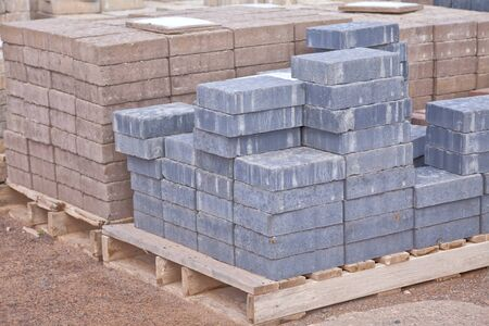 concrete: Stacks of various colored concrete pavers (paving stone) or patio blocks organized on wooden pallets and for sale in a retail setting such as a garden center or building supply.
