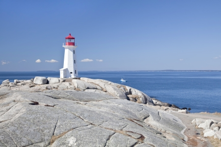 cove: Peggys Cove lighthouse, Nova Scotia, Canada.  Lobster boat gathering traps in the background. Stock Photo