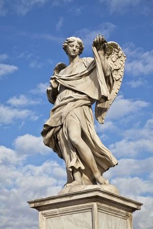 angelo: Statue of an Angel carrying a symbol of the Passion on Sant Angelo bridge Rome Italy. Angel created by renaissance artist, Bernini, against blue sky Stock Photo